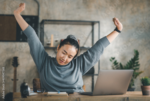 Fotografering Young Asian Business woman stretching herself and exercise for relaxation while working at home office