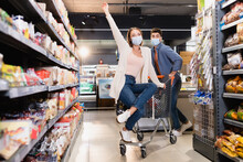 Young Woman In Medical Mask Sitting On Shopping Trolley Near Boyfriend And Groceries In Supermarket
