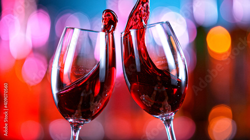 Fotografia Red Wine Glasses Hitting Together in a Bar, Cheers Concept.