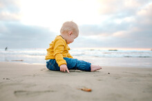 Blonde 6 Mo Old Boy In Yellow Shirt Sitting On Ocean Beach At Sunset