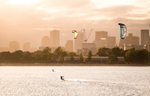 A Woman Kiteboarding On A Summer Afternoon With The Boston Skyline