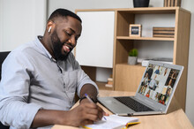 Happy African American Man Using The App For Distance Video Communication With Coworkers, Friends, Meeting Online, Looking At The Laptop Screen With People Profiles, Studying, Listening, Making Notes
