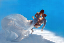 The Couple Is Dancing Or Hugging In The Pool Underwater. A Girl In A Dress With A Long Train And A Guy Swim Underwater