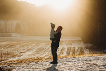Father Holding Daughter Up In Golden Field During Sunset In Winter