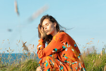 Young Woman With Long Hair And Flowery Fashion Orange Dress Posing By