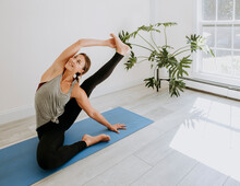 Smiling Young Woman Practice Yoga In Bright Room Front Of Sunny Window