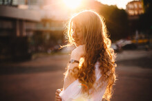 Portrait Of Happy Young Woman Standing In City At Sunset
