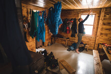 A Man Sorting And Drying Climbing Gear In A Cabin During The Day