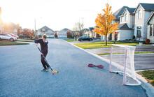 Teen Boy Playing Street Hockey Alone On A Residential Street.