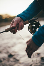 Detail Of Fly-fisherman Stripping Line While Fishing In Twilight