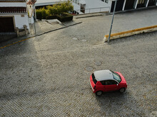 Top Down View Of Compact Red Car Driving On Cobble Stone Street