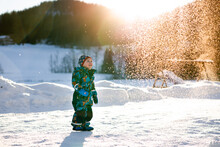 Young Boy In Farm Watching Snow Fall In Winter Wonderland On Sunny Day