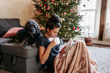 Young Woman Reading And Drinking Tea With Dog Bu Christmas Tree