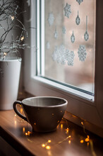 A Large Tea Cup On A Wooden Windowsill With Christmas Lights.