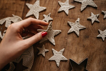 Hand Of Young Woman Creating Clay Stars As Christmas Ornaments