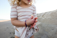 Detail Shot Of Little Girl Holding Shells On The Beach With Dress On
