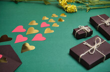 Pasting Hearts Into Brown Boxed Gifts On A Green Background