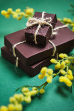 Gifts In A Brown Cardboard Box On A Green Background With Yellow Flowe
