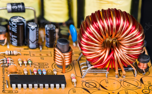 Photo Toroidal or cylindric inductors on printed circuit board with electronic components