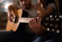 Anonymous Man Playing Guitar Near Girlfriend