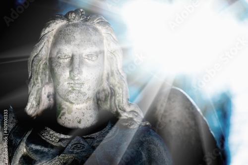 Valokuvatapetti Beautiful guardian angel in sun rays. Bery ancient stone statue.