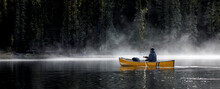 Man Paddles Canoe On Lake With Mist And Fog On Sunny Day By Forest