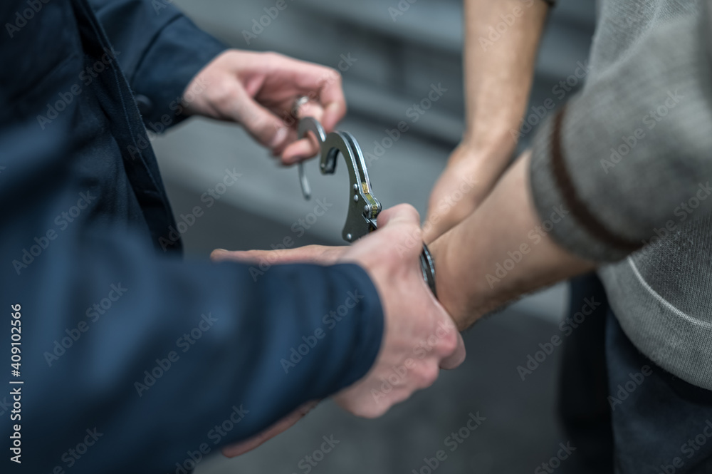 Fototapeta handcuffing the arrested person. Implementation of the arrest