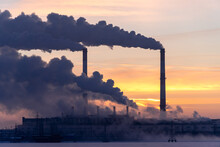 Emission To Atmosphere From Industrial Pipes. Smokestack Pipes Shooted At Sunrise. Global Warming Concept And Air Pollution