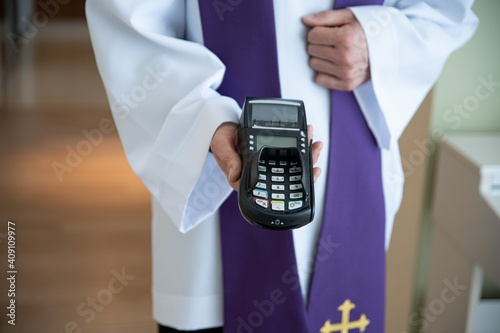Fototapeta Card reader in the hand of a priest during a pastoral visit