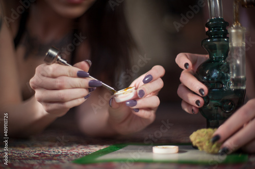 Slika na platnu Women with nicely manicured fingernails use a titanium dabber tool to scoop conc