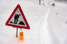 Closeup Shot Of A Road Works Sign For Construction In The Snow