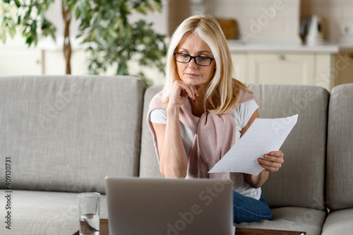 Obraz Focused senior blonde works at home remotely, sitting on the couch in the living room, analyzes monthly reports, uses a laptop. Work from home - fototapety do salonu