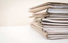 Extremely Close Up Stack Of Documents Folders On Office Desk Waiting To Be Completed