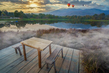 Wooden Chairs And Table In Misty Morning At Lake Side Restaurant  For Winter Vacation