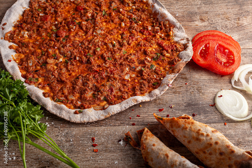 Obraz Traditional Turkish Pizza known as Lahmacun made with thin flat dough covered with mixture containing ground beef and baked in stone oven. It is served with parsley, tomatoes and onions on wood. - fototapety do salonu