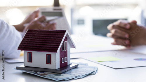 Obraz Close-up photo of a small house model, in the back there are two business people chatting. Real estate business ideas. - fototapety do salonu