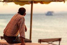 A Jordanian Man Wearing Long Sleeve Shirt Is Sitting On A Wall By The Beach In Aqaba, Jordan. He Is Watching The Ships Pass By The Gulf Of Aqaba, Red Sea With His Arm On His Knee. Peaceful Scene.