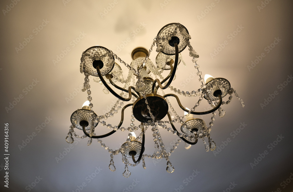 Fototapeta luxury interior details.  chandelier with glowing lamp and sparkling crystal pendant hangings. Vintage lamp on ceiling