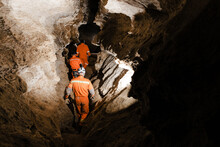 Three Men, Strong Physique, Explore The Cave. Men Dressed In Special Clothes To Pass Through The Cave And Stopped, Looking At The Map