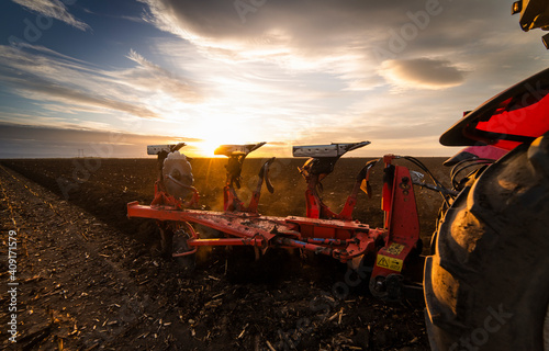Fototapeta Tractor on the field during sunset. obraz