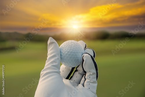 Obraz na plátne golfer showing golf ball on hand holding with green grass golf course sunlight rays background sunlight