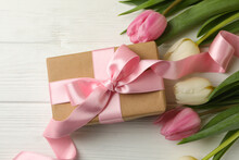 Beautiful Tulips And Gift Box On White Wooden Background
