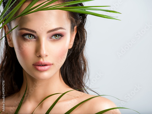Young beautiful woman with healthy skin of face and palm leaves. Closeup fresh face of an attractive caucasian girl with green plants. Model with bright brown eye makeup. Skin care concept. © Valua Vitaly