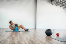 Gym Medicine Ball Workout Abs Exercise At Home. Man Working Out Core Body With Weighted Russian Twists Exercises Training.