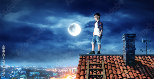 Fototapeta premium Boy on the roof and the moon.