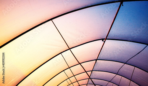 Obraz Plastic greenhouse cover with rusty frame at sunset, abstract industrial background. - fototapety do salonu