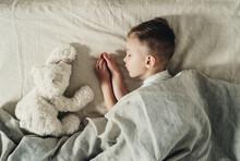 The Boy Sleeps With A White Teddy Bear On The Bed