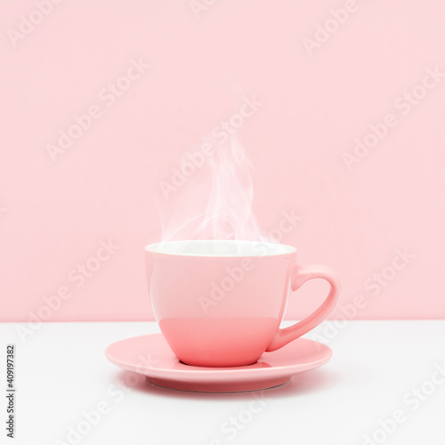 Pink cup with steam, coffee or tea on pink background. © prime1001