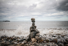Pile Of Stones Stacked Up Balancing Sea Shore Ocean Lapping Up Pebbles Tower Grey Granite With Dramatic Storm Clouds Gather Above Waves Crashing On The Shore At Seaside As Tide Comes In Holiday Resort