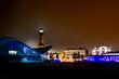 canvas print picture - Skyline Warnemünde mit Wahrzeichen Leuchtturm und Teepott bei Nacht